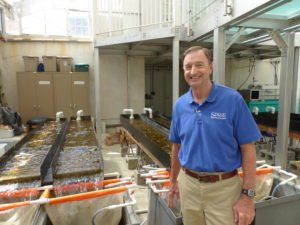 Dr. Bernard Sweeney, Senior Research Scientist and Director of the Stroud Water Research Center standing beside some of their water flumes.